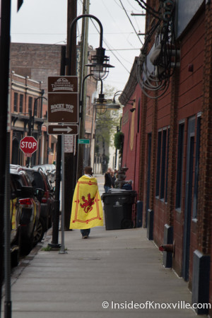 Caped Person Walking Through the Old City